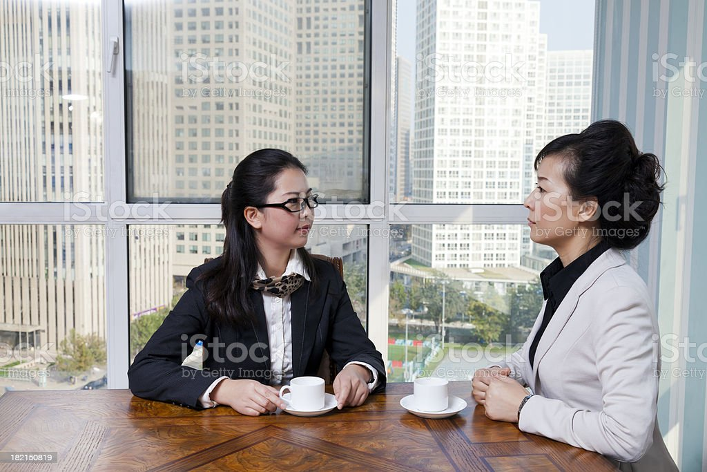 East asian female colleagues drinking coffee in office royalty-free stock photo