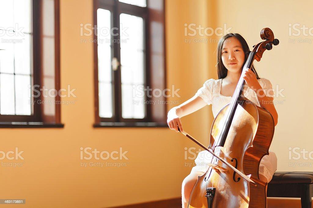 East asian teenage girl playing cello stock photo