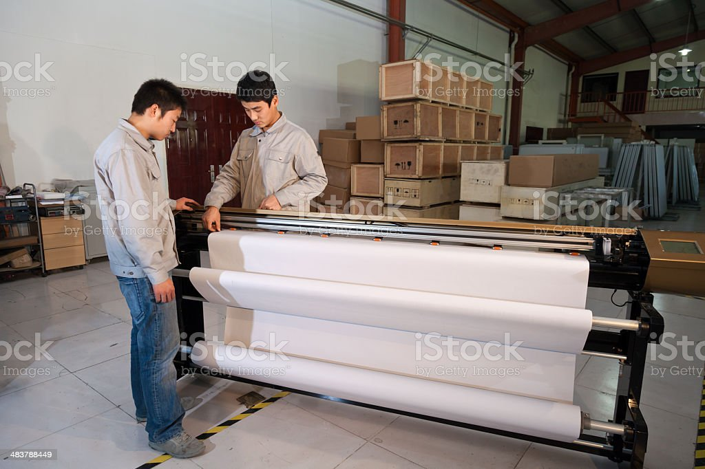 East asian workers operating the printer royalty-free stock photo