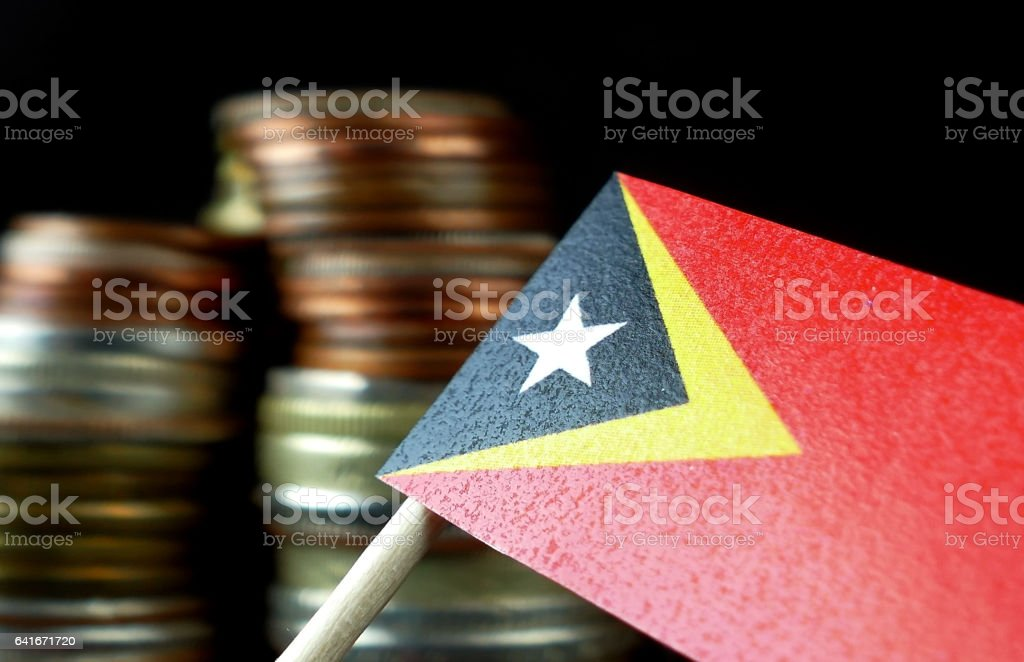 East Timor flag waving with stack of money coins macro stock photo