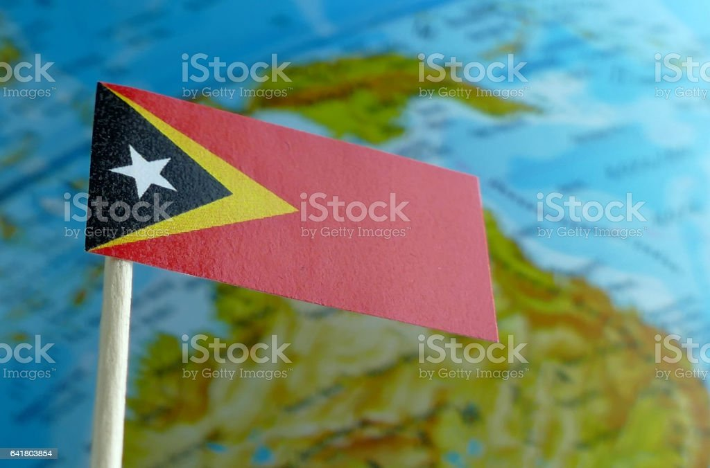 East Timor flag with a globe map as a background stock photo