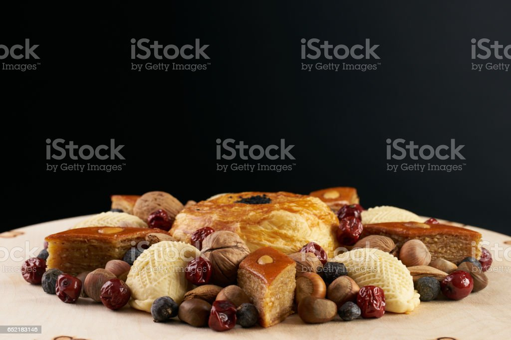 Easter and traditional sweets baklava, shekerbura, gogal ,nuts , dates on wooden table. stock photo