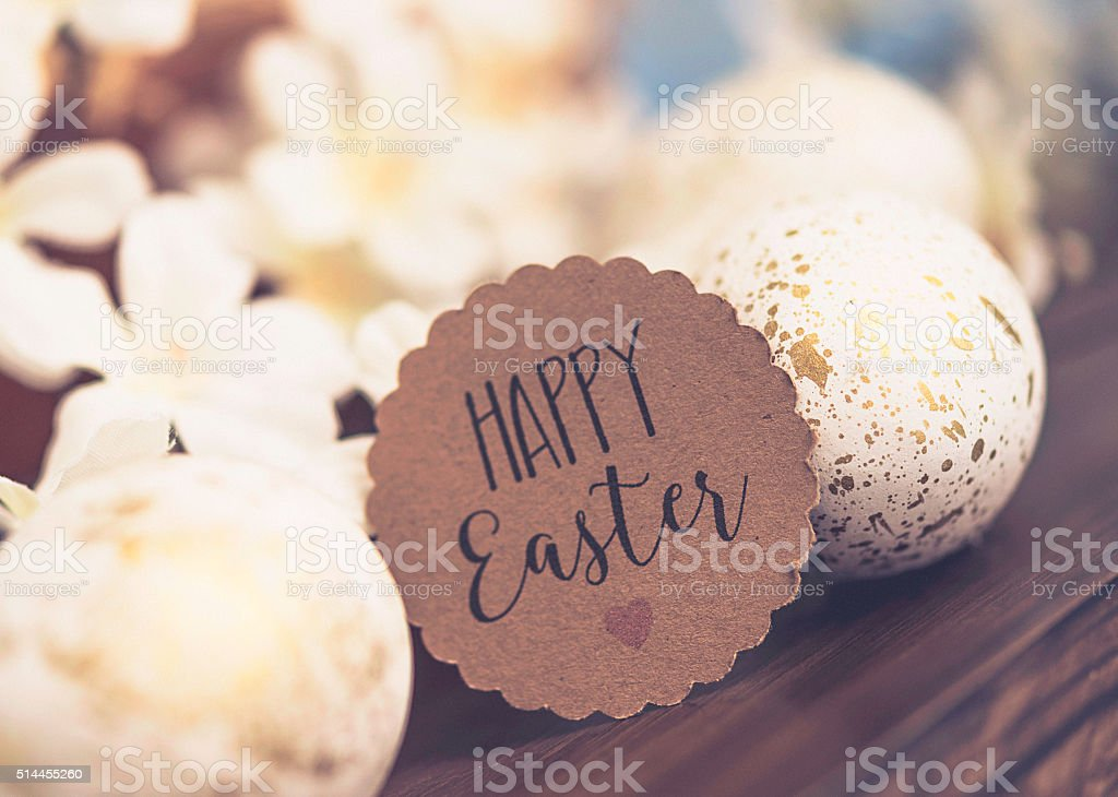 Easter arrangement with blossoms and decorated white and gold eggs stock photo