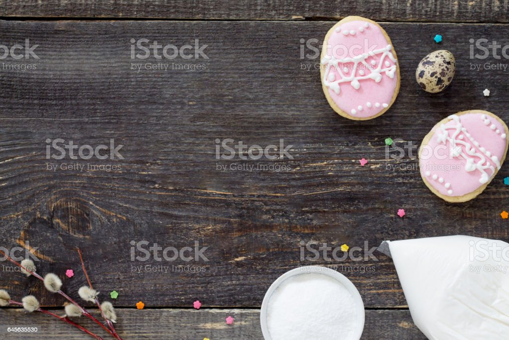 Easter background. Easter cookies and icing on a wooden table. Copy space, top view. stock photo