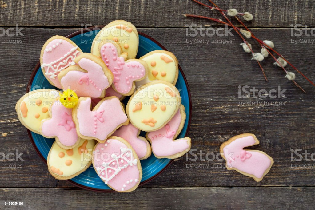 Easter background. Easter cookies on a plate and twigs of willow on a wooden table. Easter recipe. stock photo