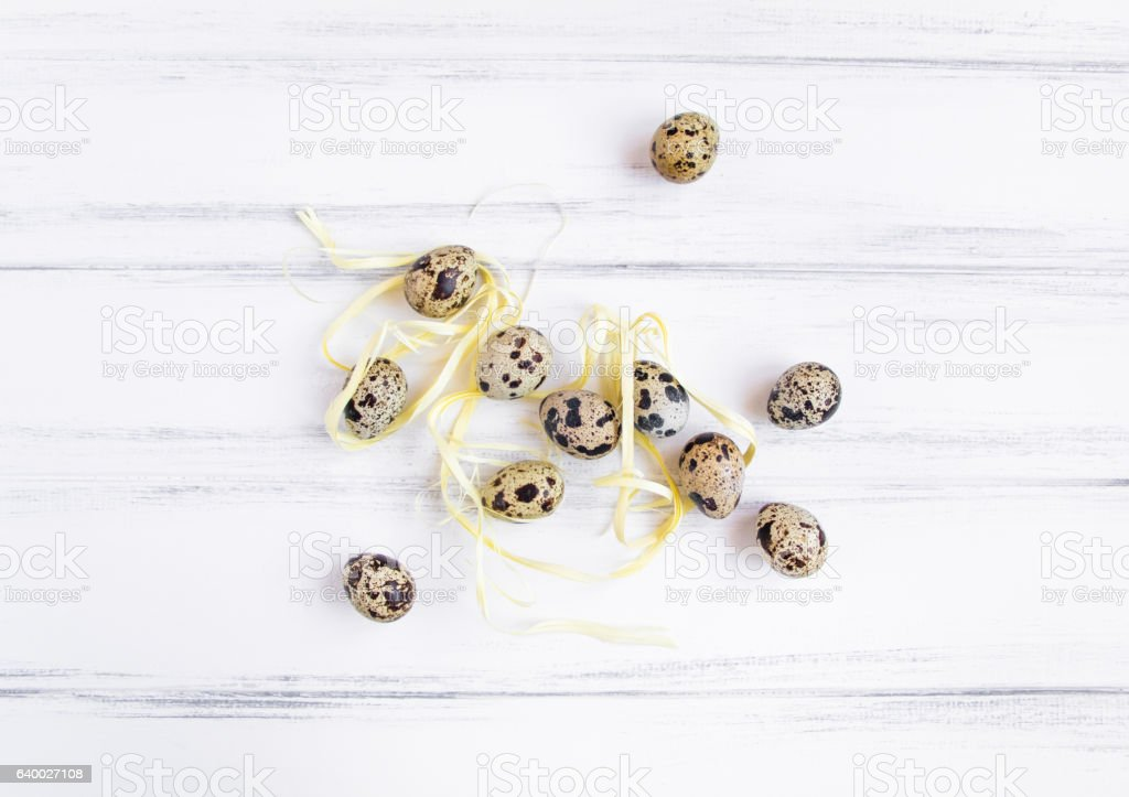 Easter background, quail eggs on white wooden table. Flat lay stock photo