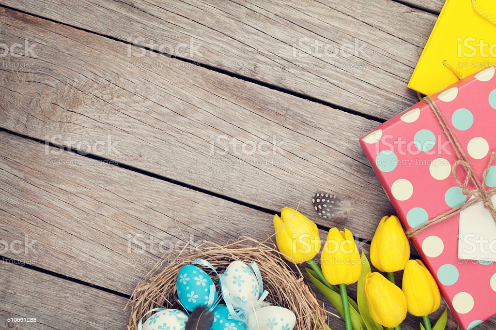 Easter background with eggs in nest, yellow tulip stock photo