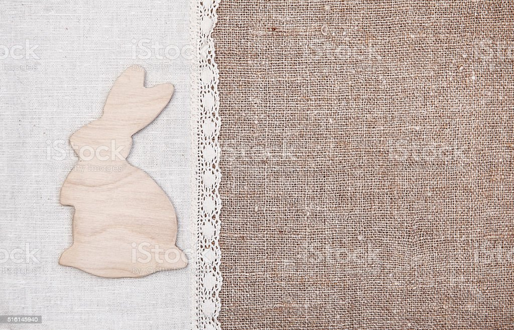 Easter background with wooden rabbit on the burlap stock photo