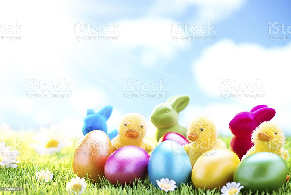 Easter bunnies and eggs on meadow with cloudy sky background royalty-free stock photo