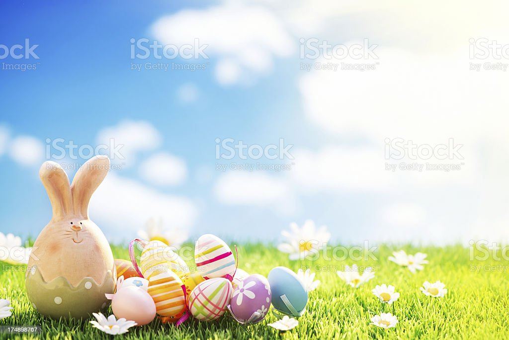 Easter bunny and eggs on meadow with cloudy sky background royalty-free stock photo