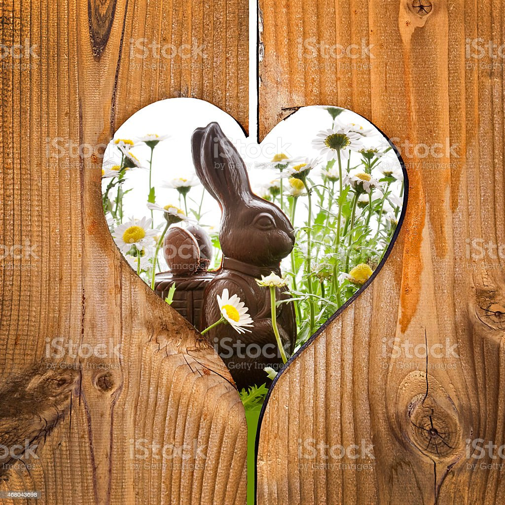 Easter Bunny behind a wooden heart stock photo