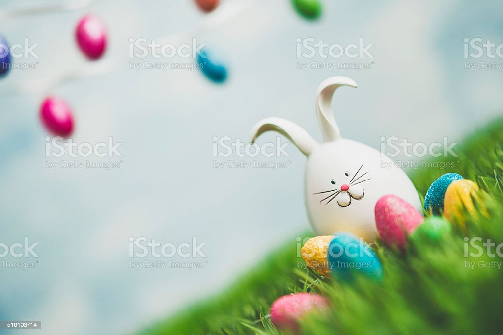 Easter bunny in grass with Easter egg garland stock photo