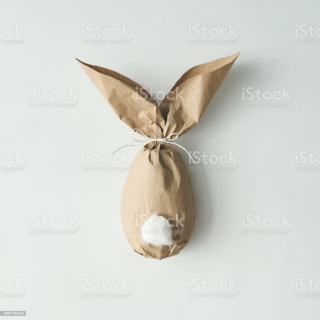 Easter bunny paper gift egg wrapping diy idea. Minimal easter concept stock photo
