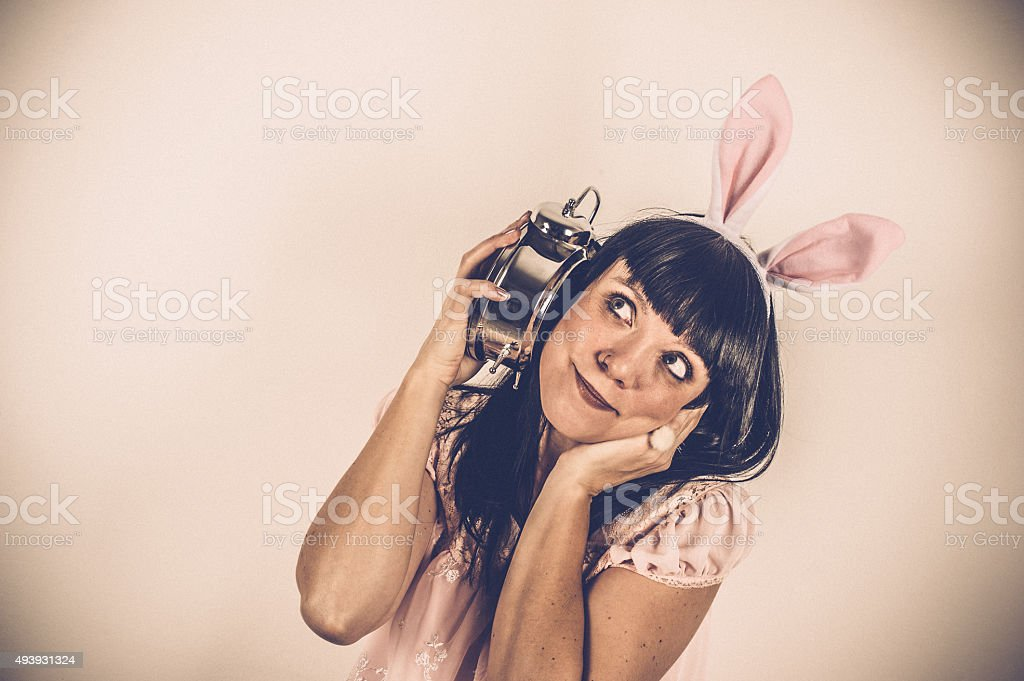 Easter Bunny weared Woman with Alarm Clock stock photo