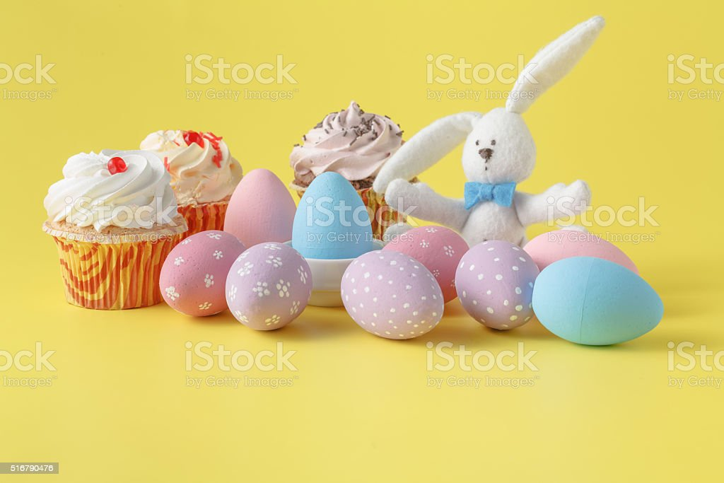 Easter bunny with egg on yellow background stock photo