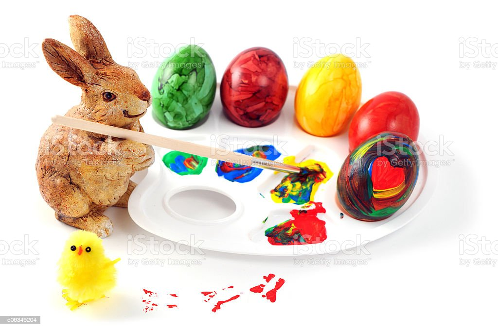 easter bunny with paint palette and brush painting easter eggs stock photo