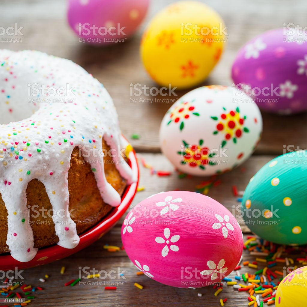 Easter cake and colorful eggs on kitchen table. stock photo