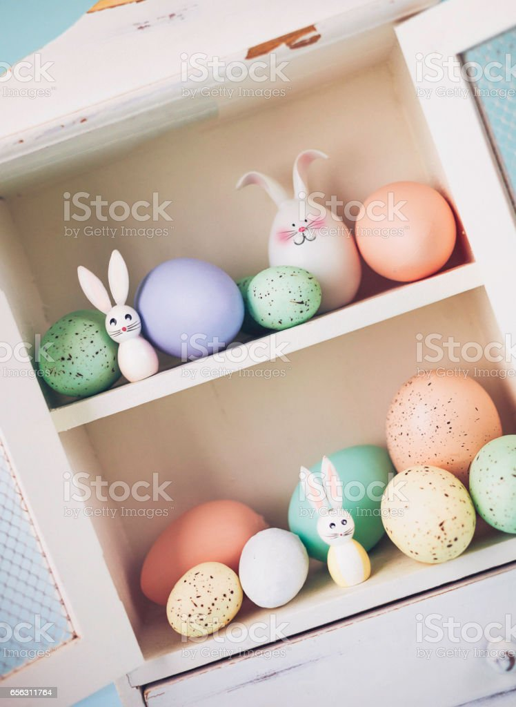 Easter collection of eggs and rabbits in white cabinet stock photo