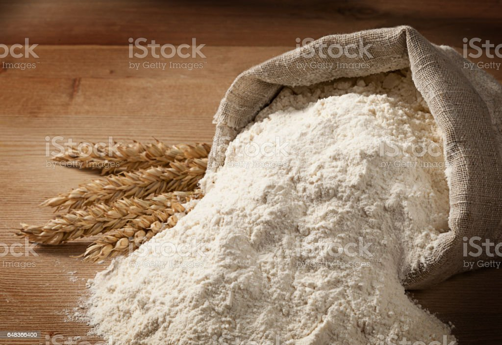 Easter concept with copyspace. Flour spilled out of the bag and ripe ears on an old table. stock photo