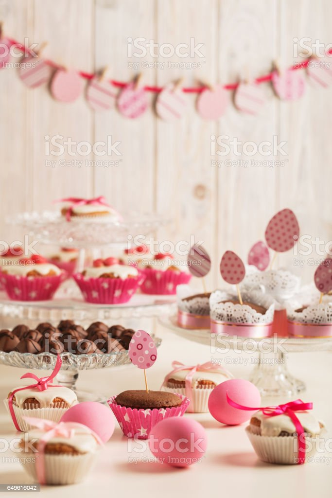 Easter cupcakes decorated with pink candy, paper eggs and ribbons. stock photo