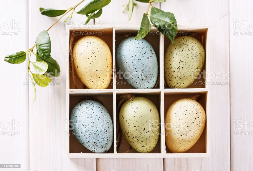 Easter decor eggs in a box over wooden background stock photo