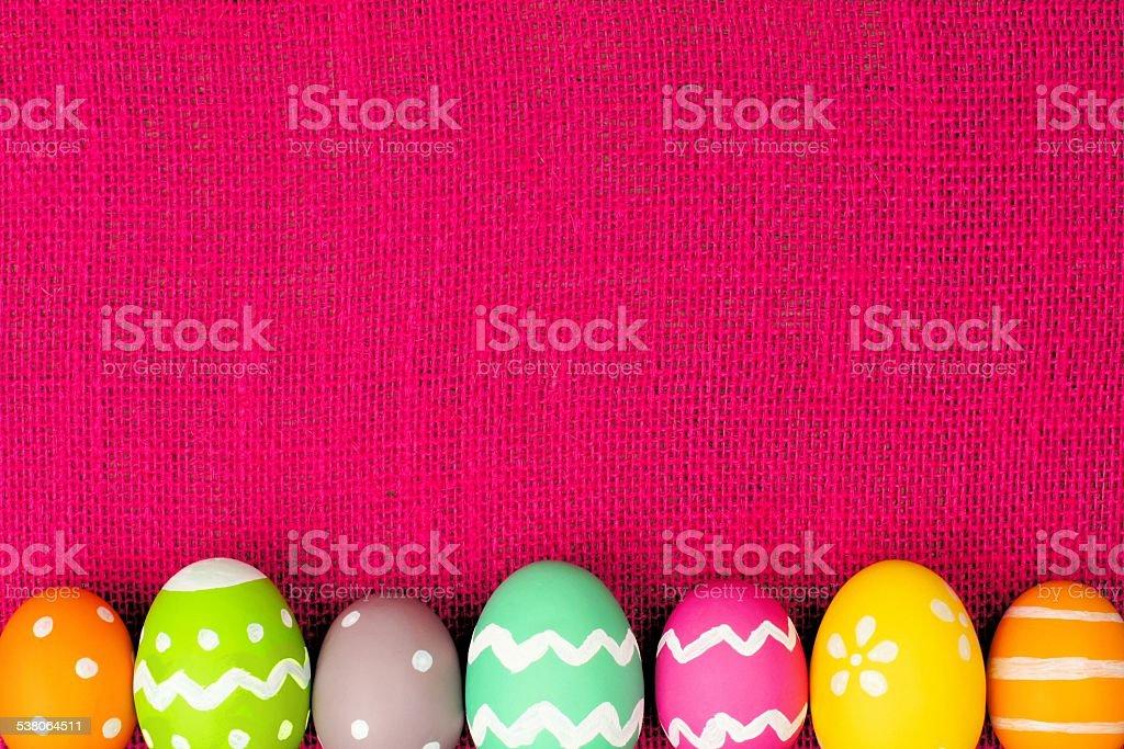 Easter egg border on pink burlap background stock photo