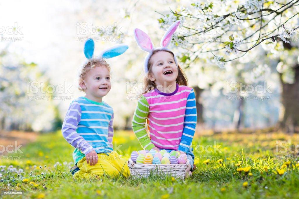 Easter egg hunt. Happy kids with bunny ears in garden. stock photo
