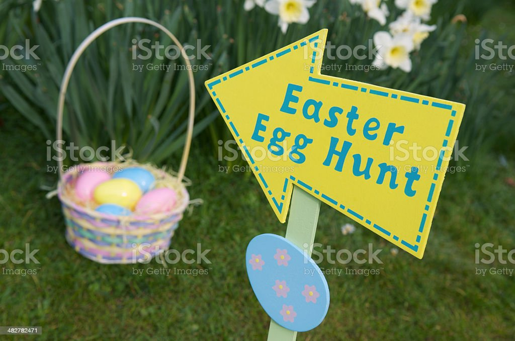 Easter Egg Hunt Sign with Basket in Spring Field stock photo
