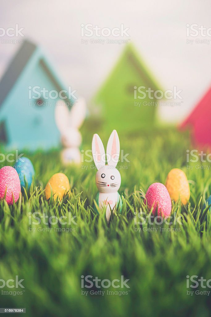 Easter egg hunt with vintage wood bunnies and Easter eggs stock photo