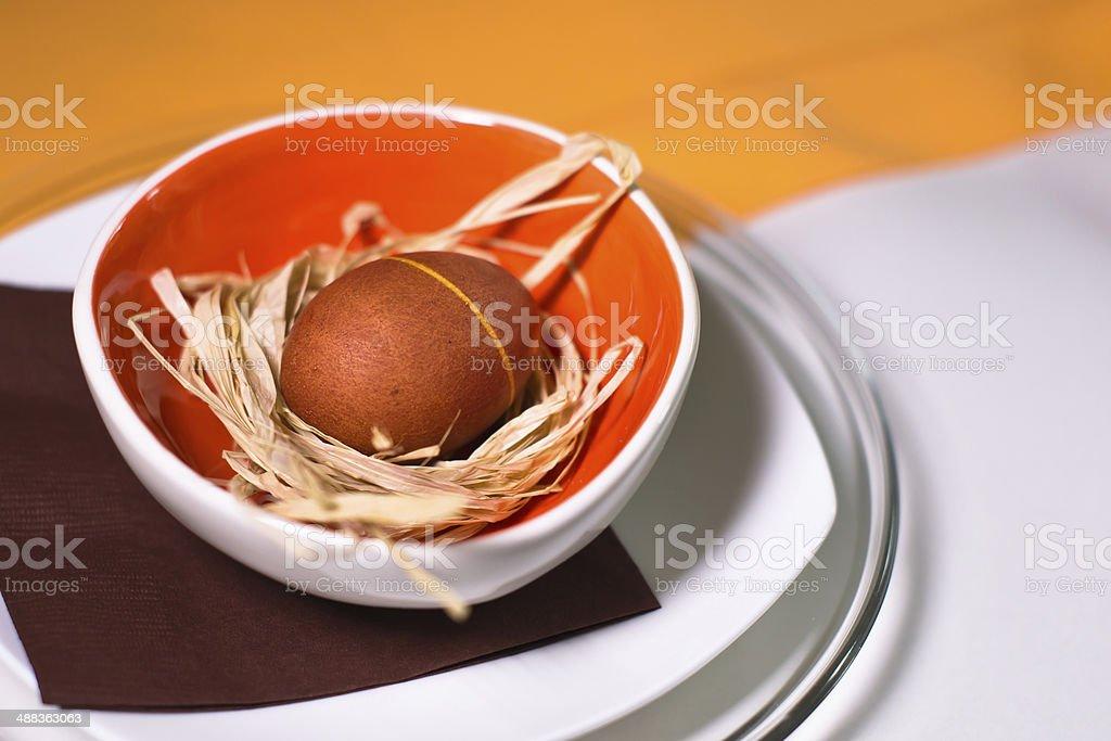 Uovo di Pasqua sulla paglia nel piatto colorato e Tovaglia foto stock royalty-free