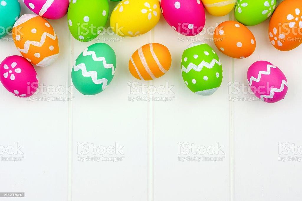 Easter egg top border against white wood stock photo