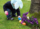 Easter egg with a boy finding plastic eggs