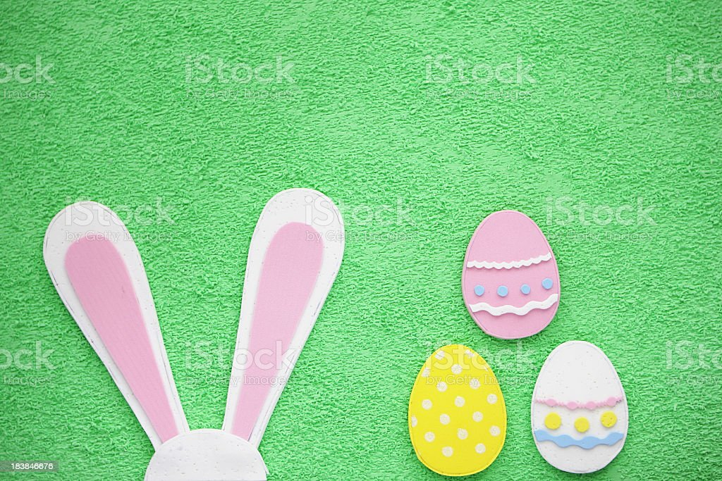Easter eggs and bunny ears on green background royalty-free stock photo