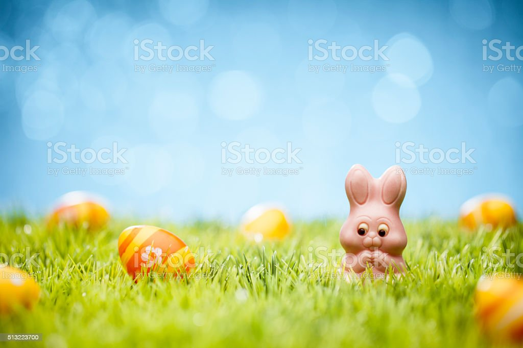 Easter Eggs and candy Bunny - Green Grass Defocused Bokeh stock photo