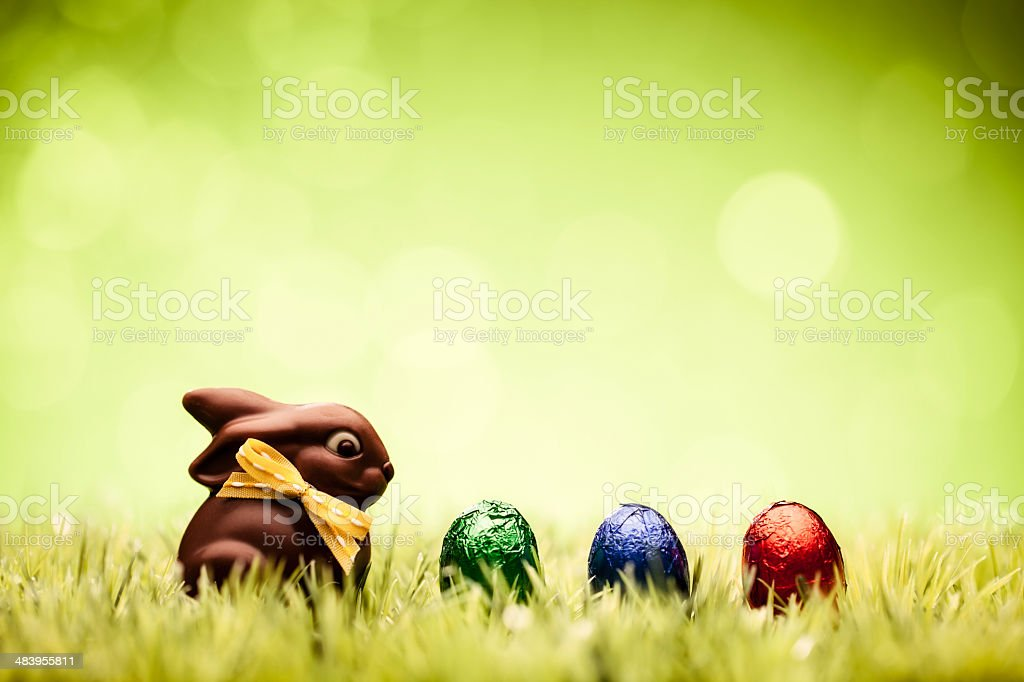 Easter Eggs and Chocolate Bunny - Green Grass Defocused Bokeh stock photo