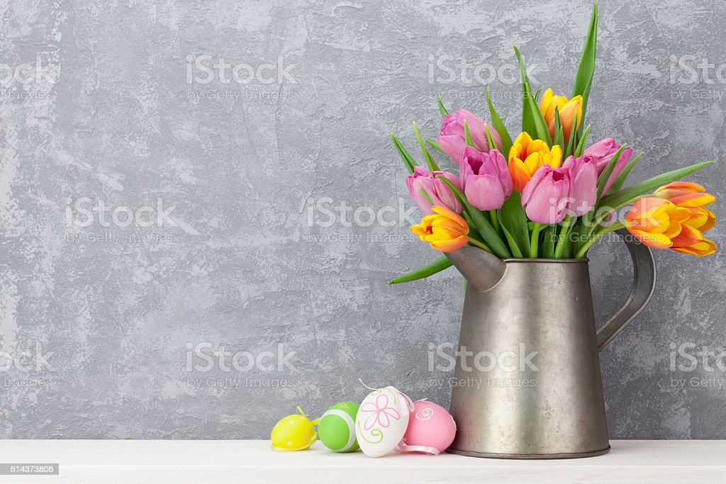 Easter eggs and colorful tulips bouquet stock photo