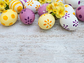 Easter eggs and primula flowers composition on the white wooden