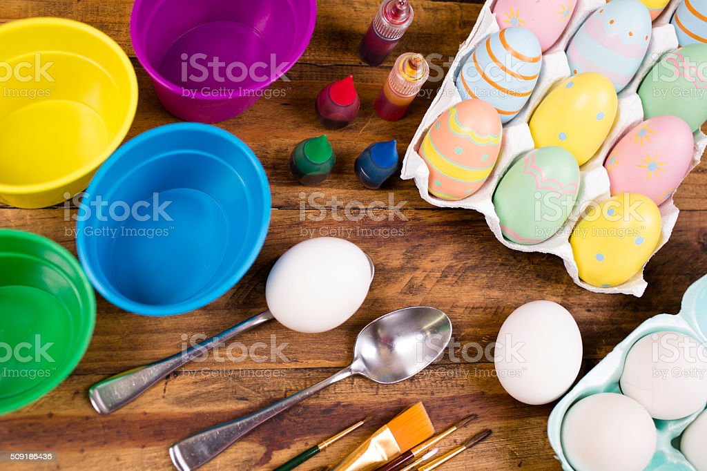 Easter eggs being decorated on wooden table. Decorating supplies. stock photo