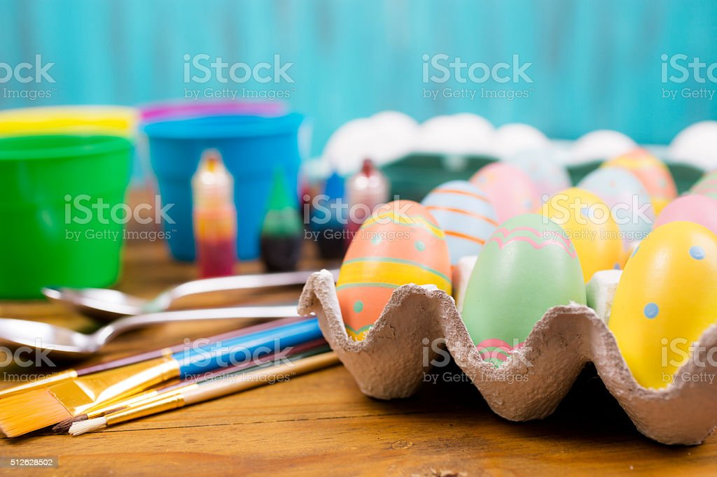 Easter eggs being decorated on wooden table. Supplies. stock photo