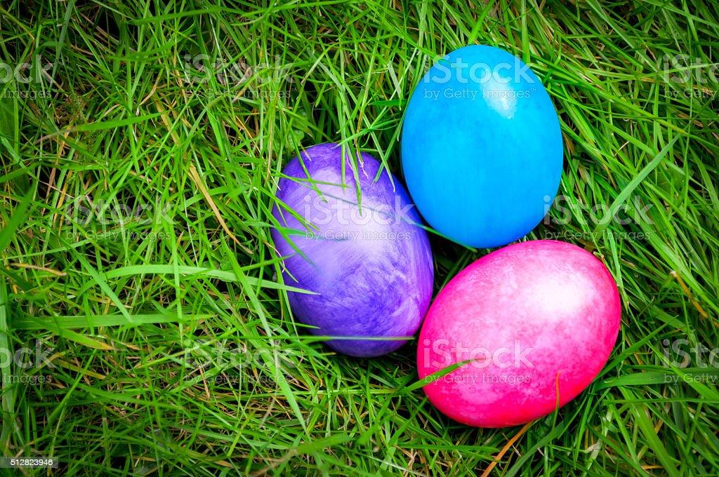 Easter eggs deep into green grass stock photo