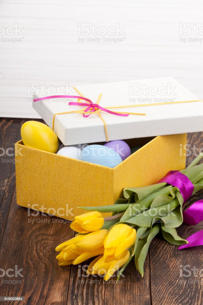 Easter Eggs in a box with colorful tulips stock photo
