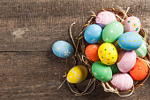 Easter eggs in a nest on wooden background