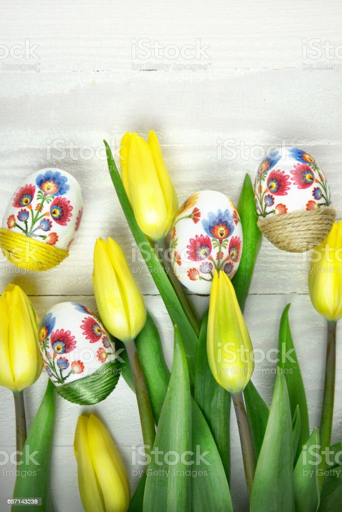 Easter eggs in hand made decoupage decoration with yellow tulips stock photo