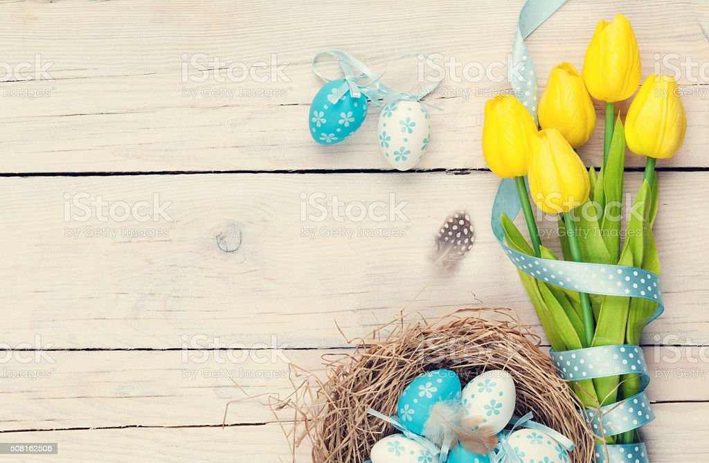 Easter eggs in nest and yellow tulips stock photo
