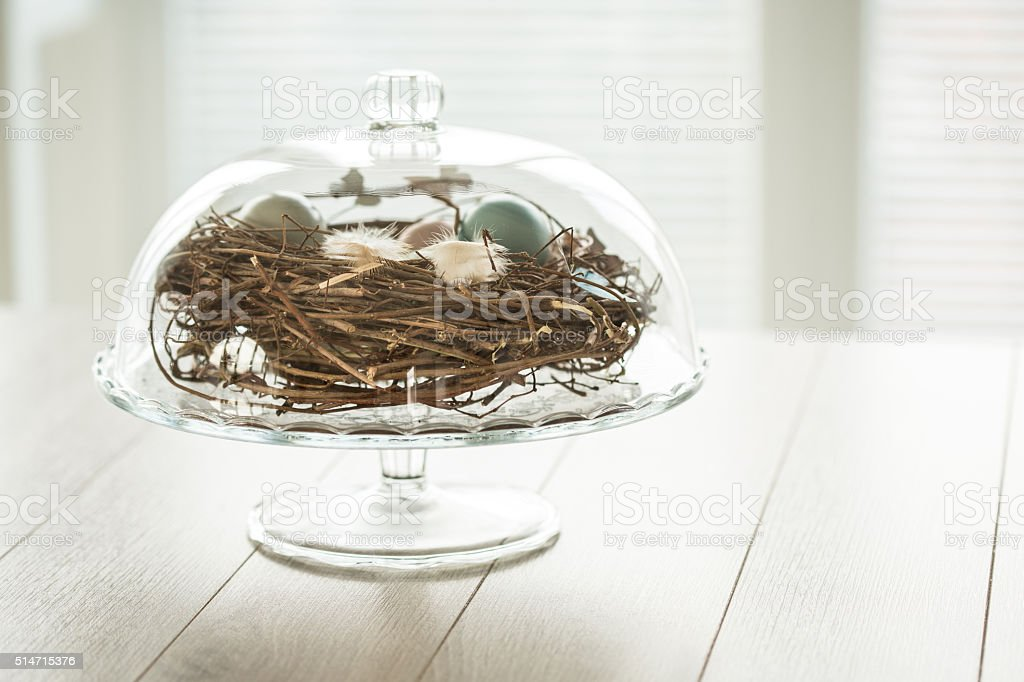 Easter eggs in nest on cake stand stock photo