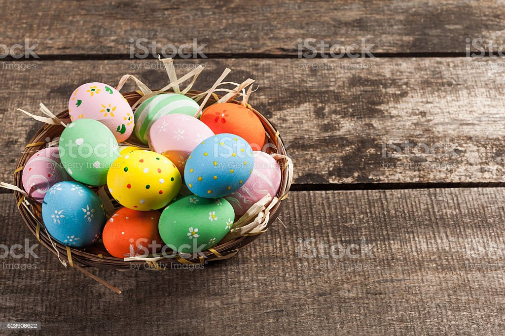 Easter eggs in nest on wooden background stock photo