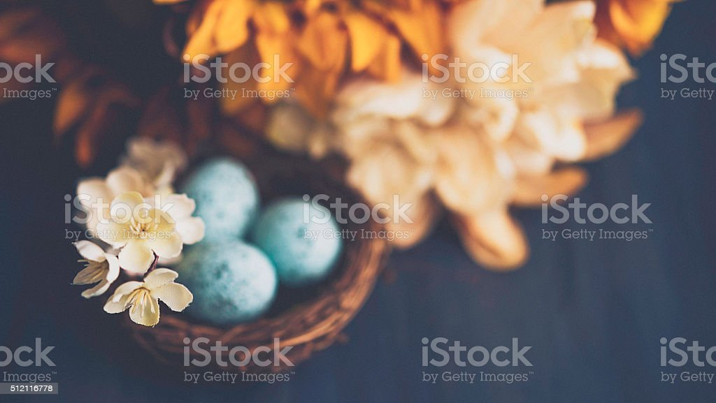 Easter eggs in nest with sunflower and blossoms arrangement stock photo