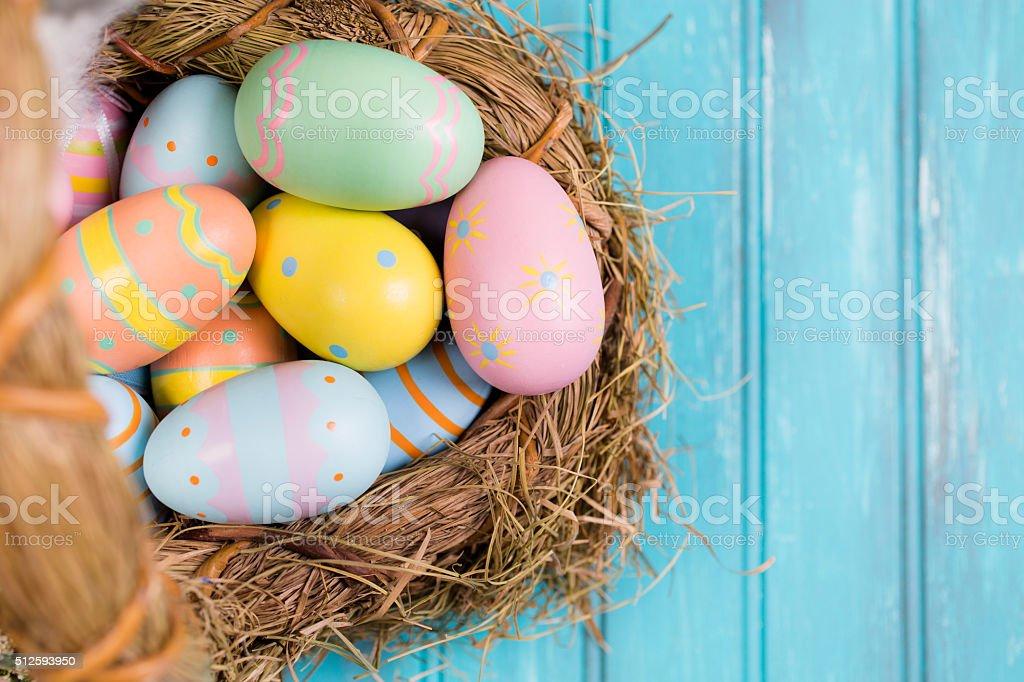 Easter eggs in straw basket on blue wood.  Seasonal background. stock photo