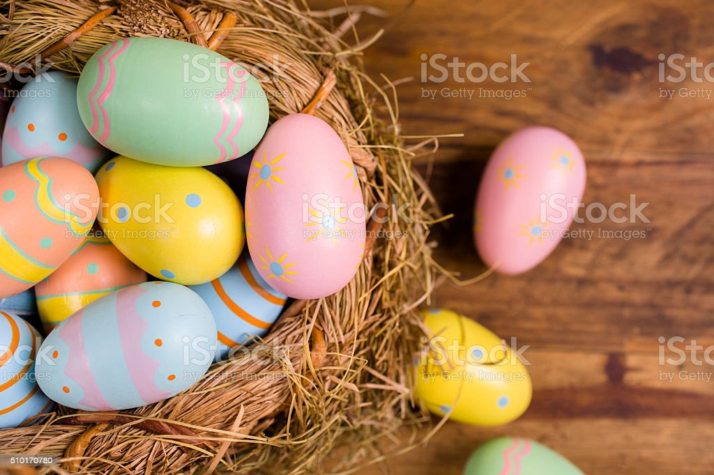 Easter eggs in straw basket on rustic wood table. stock photo