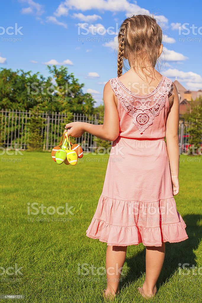 Easter eggs in the hands of a little adorable girl stock photo